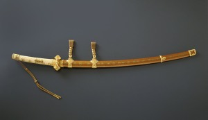 Mounting for a ceremonial long sword (tachi) with nine planet family crests and gold fittings, Japan. Edo period (1615–1868), 19th century. Lacquered wood with sprinkled gold (makie) decoration, gilt bronze, gold, ray skin, leather. Eisei Bunko Museum, 29241. © Eisei Bunko, Japan.