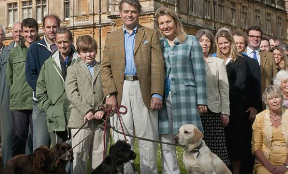 "Lady Fiona Carnarvon (in blue plaid) is the down-to-earth duchess who actually lives at Downton Abbey (Highclere Castle).  Here, she is pictured with her husband, Geordie, the Earl of Carnarvon, her beloved dogs, and some of the 90 people who form the crew of the internationally acclaimed ""Downton Abbey."""