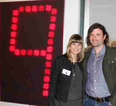 "Ann Trinca, curator of ""Napa Valley Collects,"" at the exhibition's opening with Rob Ceballos, Director of the Hess Art Collection.  Behind them is Alan Rath's ""Huge Pi 500"" (1996) aluminum, acrylic, custom electronics, LEDs—a digital sculpture that clicks through the infinite digits of the mathematical series Pi. Rath gave a presentation on his art and electronic media at the Hess Collection on April 27, 2013.  Photo: Geneva Anderson"