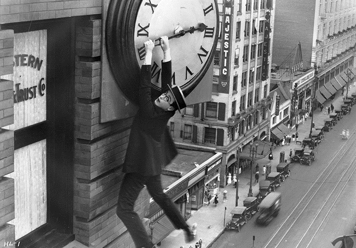 "Harold Lloyd's romantic silent comedy ""Safety Last"" (1923) closes the San Francisco Silent Film Festival and includes one of silent film's most iconic images—Lloyd clutching the hands of a giant clock while dangling from ledge of a skyscraper above moving traffic.  Lloyd's performance cemented his status as one of the leading figures in early motion pictures.  The film's title is a play on the expression, ""safety first,"" which emphasizes safety as the primary means of avoiding accidents.  Image: courtesy SFSFF."