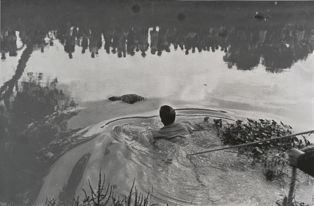 """Enrique Metinides worked as a crime photographer in Mexico for over 50 years capturing murders, car crashes, and catastrophes for the nota rojas, Mexico's infamous crime magazines.  """"Rescate de un ahogado en Xochimilco con público reflejado en el agua,"""" (Retrieval of a drowned body from Lake Xochimilco with the public reflected in the water), 1960; gelatin silver print; 13.75 x 20.75 inches; SFMOMA, Anonymous Fund purchase; © Enrique Metinides"""