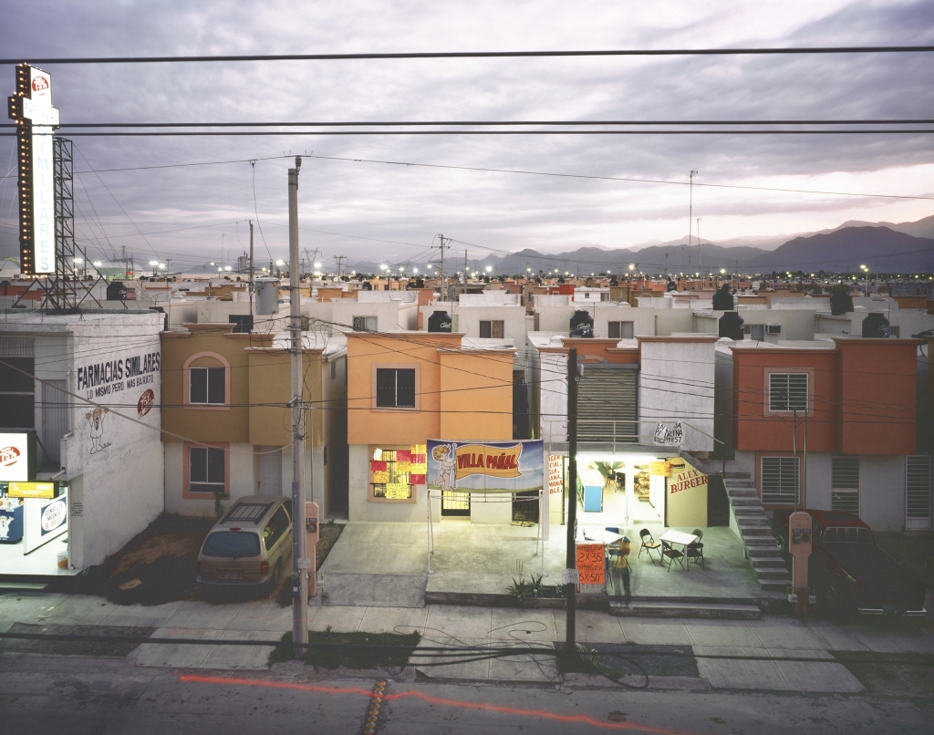 """9.Questions of land use and urban development pervade the work of contemporary Mexican photographer Alejandro Cartagena.  The stillness belies the violence that has a vice-grip on Mexico's northern cities as the drug war has relocated to the suburbs. """"Business in a Newly Built Suburb in Juarez,"""" from the series Suburbia Mexicana, 2009; inkjet print; 15 3/4 in. x 20 in.; Collection SFMOMA, Accessions Committee Fund purchase; © Alejandro Cartagena"""