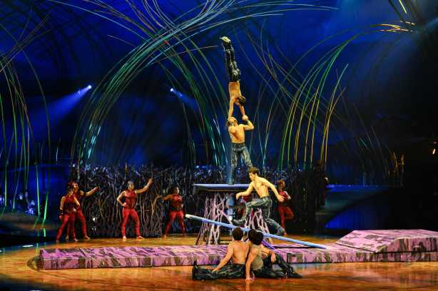"In ""Amaluna's"" daring Teeterboard act, young men launch themselves high into the air, twisting and turning in a playful high-speed attempt to escape from their prison. They pull off several seemingly impossible feats, like landing in a handstand on another performer's upturned palms.  Costume credit: Mérédith Caron; Photo: Laurence Labat, Cirque de Soleil"