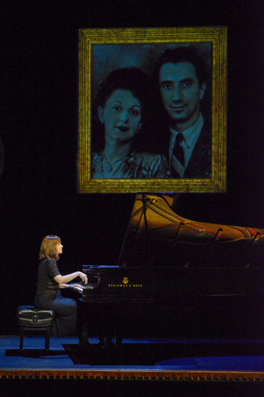 "In ""The Pianist of Willesden Lane,"" award-winning pianist Mona Golabek plays the piano under a projected image of her parents, Lisa and Michel Golabek.  Photo courtesy of mellopix.com"