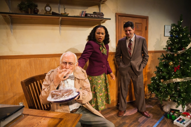 "Gloria Weinstock (center) is kindhearted Jesse in ""Storefront Church"" at San Francisco Playhouse.  Her financial woes become significant when she ""rents"" the ground floor of a store front to Chester, an impoverished Pentecostal preacher whose church was destroyed in the Katrina hurricane.  In Chester's three months of occupancy, he has not paid Jessie and she has financed all the ""upgrades"" to the church by taking out a second mortgage.  Her husband Ethan (Ray Reinhardt) (left) goes to bat for her at the bank and she asks Donaldo (Gabriel Marin) (right), the Bronx Borough president, and her best friend's son to assist her."