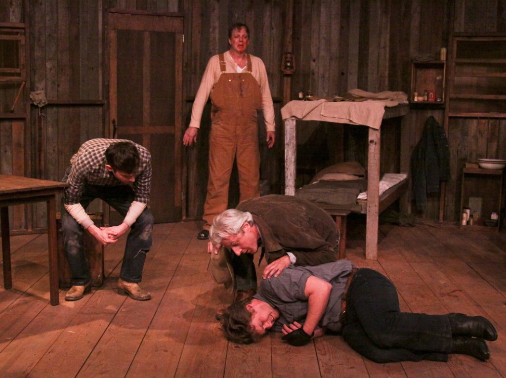 "Cinnabar Theater in Petaluma presents Steinbeck's masterpiece ""Of Mice and Men,"" featuring (L to R) Kevin Thomas Singer, Samson Hood, Tim Kniffin, and James Gagarin.  After the boss's son Curley attacks Lennie for no good reason, Lennie squeezes Curley's hand too hard and crushes it.  Slim tends to Curley while lumbering Lennie is shocked at what he has done.  Photo by Eric Chazankin"