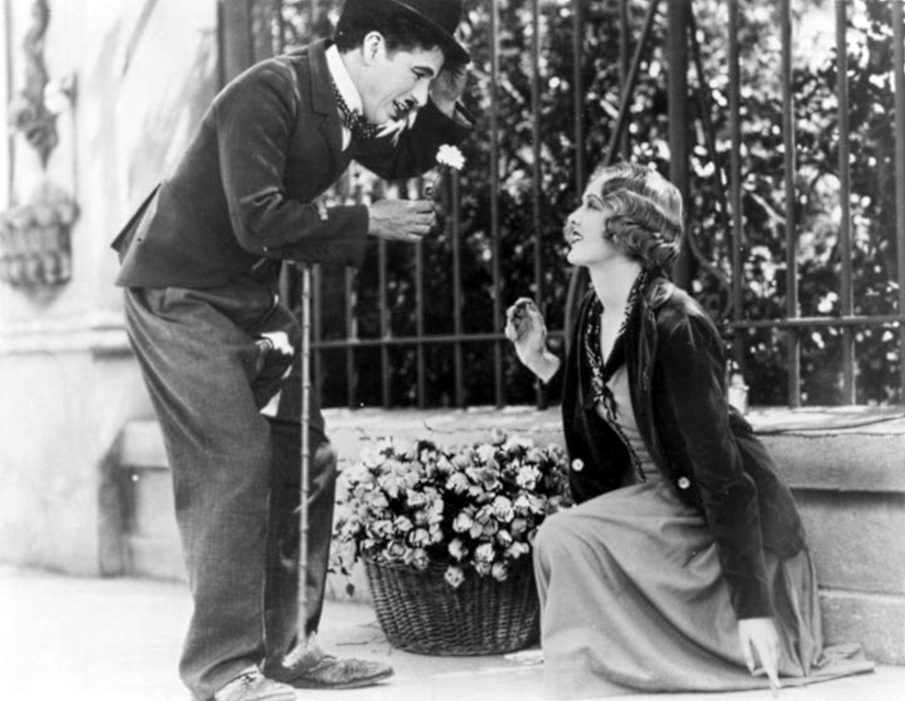"Charlie Chaplin's Little Tramp buys a flower from the blind flower girl, played by Virginia Cherrill, in the silent film classic, ""City Lights,"" which will be shown Saturday, April 12, 2014 at Davies Symphony Hall.  Guest conductor Richard Kaufman, who has devoted much of his career to the music of film, will conduct the San Francisco Symphony in live accompaniment."