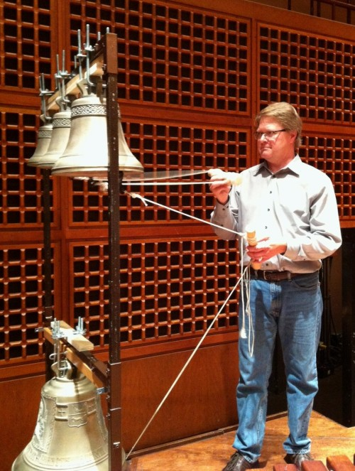 "San Francisco Symphony regular guest percussionist Victor Avdienko at Davies Symphony Hall learning the ropes, literally, of Russian bell playing.  The bell clappers (the striking implement suspended within the bell) are attached to strings and are either manipulated by a hand by pulling them or by foot pedals for the larger bells.  Saturday's ""All Tchaikovsky"" concert at Weill Hall and lawn will mark SFS' first use of authentic Russian bells in a performance.  Image: courtesy Lisa Petrie, SFS."