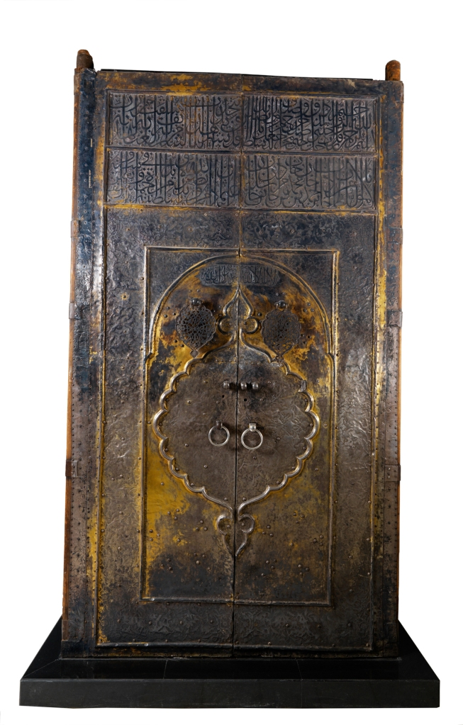"""The massive wooden gilded silver door of the Ka'ba, over 11 feet tall and nearly 6 feet wide, is one of the largest artifacts on display in """"Roads of Arabia.""""  The door was created by the Ottomans nearly 400 years ago and donated to Mecca by sultan Murad IV (reigned 1623-40).  A tenth-century poet relates that the door at that time was """"covered with inscriptions, circles and arabesques in gilded silver.""""  It bears evidence of centuries of pilgrims touching its surface. Image: courtesy of National Museum of Saudi Arabia, Riyadh, 1355/1–2."""