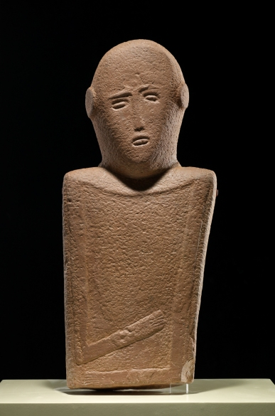 Anthropomorphic stele, 4000–3000 BCE. Saudi Arabia; Qaryat al-Kaafa site, El-Maakir city. At the entrance to Roads of Arabia, at the Asian Art Museum, three anthropomorphic sandstone steles (vertical slabs of stone used for commemorative purposes), greet visitors.  Dating to some six thousand years ago, they appear quite modern, simple and abstract but exert a very mystical, almost hypnotic, pull on the viewer.  The three figures on display are part of a group of several dozen steles, all with distinct clothing and appearance, found in an area that extends from present-day southern Jordan to Yemen.  Scholars propose that they were probably associated with religious or burial practices. Courtesy: National Museum of Saudi Arabia, Riyadh, 998.
