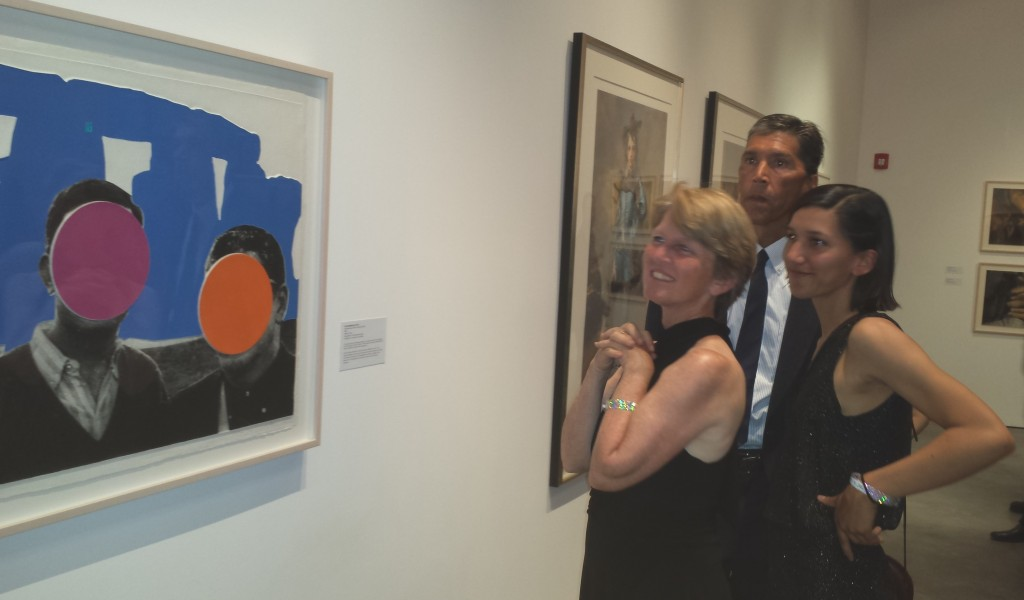 """The Morales family of Santa Rosa—Erin John and daughter Taylor (visiting from UCLA)—admire John Baldessari's mixed graphic """"Stonehenge (with Two Persons) Blue"""" (2005) (edition 12/60).  After attending the party and seeing the new collection, the family made the decision to join SCM."""