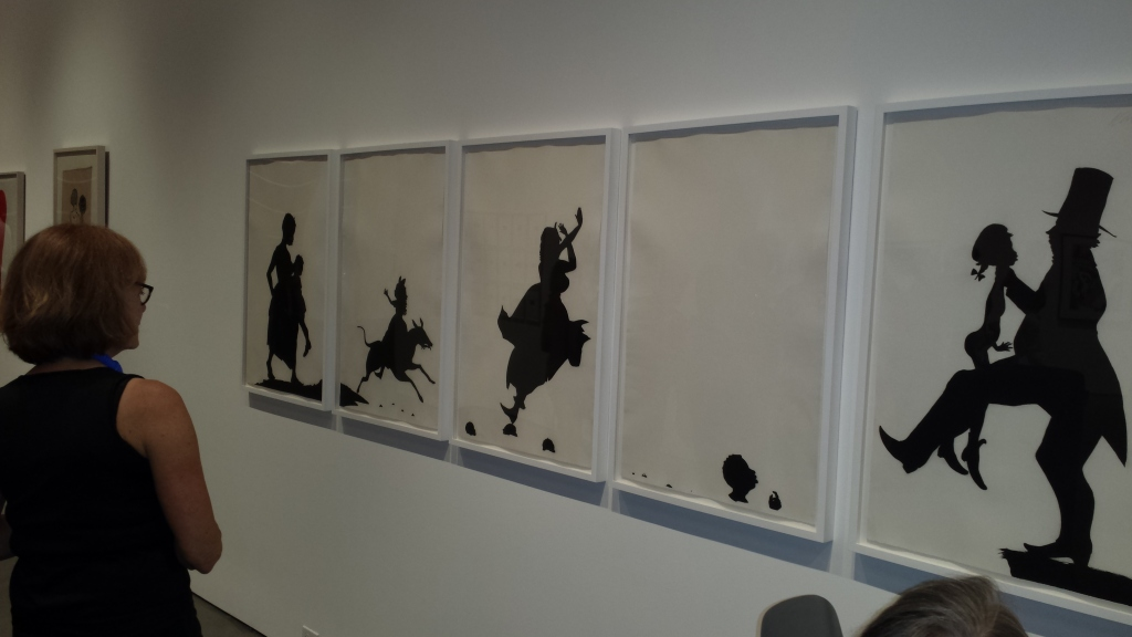 """Photographer and SRJC Photography Professor, Renata Breth, examines Kara Walker's roomsize cut-paper silhouette mural, """"The Means to An End…A Shadow Drama in Five Acts,"""" (1995) which uses provocative imagery and simple black and white cutouts to comment on racism, sex, violence, and black history.   """"She's so consistent with her ideas and execution, said Breth.  """"This piece is acting on many levels to engage our senses."""""""