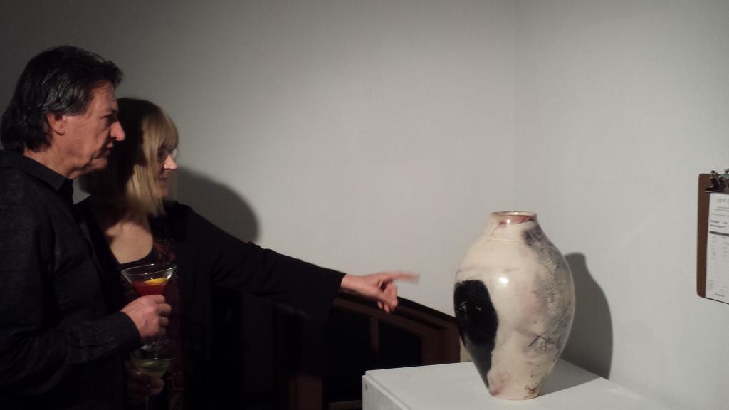 Steve and Jill Plamann admire Forestville artist, Joel Bennett's, ceramic moon vessel which garnered the most bids in the silent fundraising auction in the upstairs gallery.  Plamann owns Hammerfriar Gallery in Healdsburg.