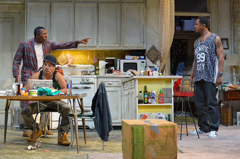 "Walter ""Pops"" Washington (Carl Lumbly, left) argues with his son, Junior (Samuel Ray Gates, right), while Oswaldo (Lakin Valdez, center) reads the newspaper in Stephen Adly Guirgis's Pulitzer Prize–winning dark comedy,"