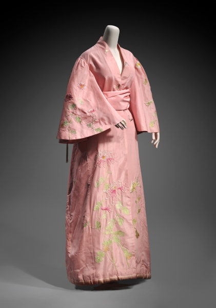 Interest in Japan grew wildly during the 1860's as shops selling Japanese goods sprang up in Paris, London and other locales. Exotic kimonos and Japanese-style designs were coveted. Kimonos appeared in opera and theater productions and artists placed them in their paintings. Parts of kimono fabric were also used in western-style dresses and capes. This women's silk taffeta dressing gown (circa 1900) was created for the Western market and retailed by Takashimaya. Elaborately embroidered with silk chrysanthemums, it represents the sumptuousness that was appreciated in the West. Typically, kimono designs sold in the West combined greenery and flowers of the four seasons─plum blossoms, cherry blossoms, irises, chrysanthemums─along with more abstract motifs such as undulating vertical lines or horizontal curves representing water. Museum of Fine Arts, Boston, Gift of Elizabeth Ann Coleman, 2001.933.1–2. Photograph © 2015, MFA, Boston.