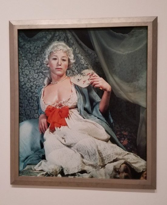 "Cindy Sherman, Untitled #193, 1989, chromogenic color print. Sherman describes the subject as ""an older Madame de Pompadour."" Her pearls are tucked slightly under her fake breastplates, and in the bottom right of the photo, a large foot pokes out from under her dress. The portrait is part of a series resulting from Sherman's collaboration with Artes Magnus and Limoges, which has ties to the French court. Broad Collection."