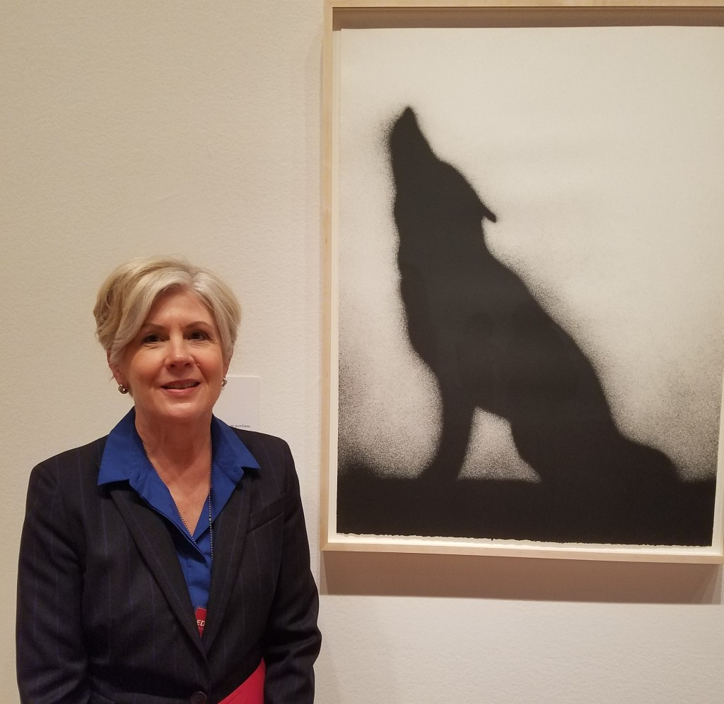 """Karin Breuer, curator of """"Ed Rusha and the Great American West"""" and curator in charge of the Achenbach Foundation for Graphic Arts, pictured with Ed Ruscha's """"Coyote,"""" a 1989 lithograph in the FAMSF collection. Photo: Geneva Anderson"""