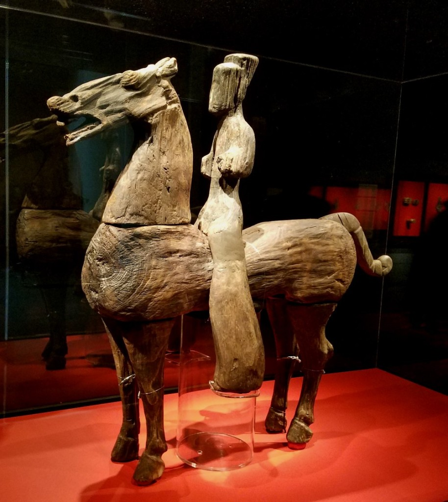 A Western Han period, 1st century BCE, carved wooden Cavalry figurine unearthed from Yandai Mountain (Yizheng, Jiangsu) represents the perfect marriage of material and subject. Both the form of horse and rider are carved exquisitely in an abstract manner allowing the natural grain of the wood to complete the idea. The end result is anything but simplified—highly stylized figuration. Many such figurines were finely carved and then painted to take on the attributes of their real-life counterparts; this one is more roughly carved. This work was excavated from a large tomb possibly belonging to a high ranking royal member of the Guangling kingdom. Among some 400 burial objects unearthed were 126 wooden figurines of warriors and attendants that formed a long procession. Just ten cavalry figurines were mounted on horses making this piece exceptionally rare. On loan from the Yizheng Museum.